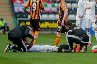 SWANSEA, WALES - APRIL 04:Kyle Naughton of Swansea city is treated on the field after being brought down David Meyler of Hull City   during the Premier League match between Swansea City and Hull City at Liberty Stadium on April 04, 2015 in Swansea, Wales.  (photo by Athena Pictures)