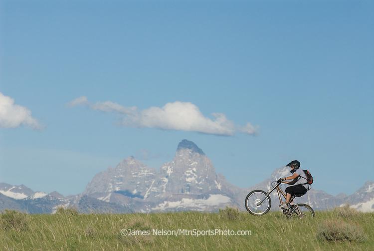 A mountain biker rides a wheelie on a ridgeline in the Big Hole Range of eastern Idaho, with the Teton Range of western Wyoming on the horizon.