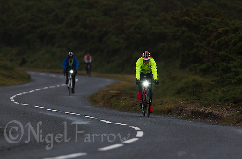 10 JUN 2011 - BRANSGORE, GBR - As dusk falls competitors turn on their bike lights and put on reflective clothing so ready to continue racing through the night during the Triple Enduroman race at the  Enduroman Ultra Triathlon Championships .(PHOTO (C) NIGEL FARROW)