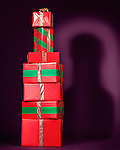 Pile of red gift wrapped Christmas presents stacked in a shape of an alcoholic beverage bottle, holiday concept.