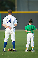 David Wood (64) of the Burlington Royals and a young baseball player during the National Anthem at Burlington Athletic Park in Burlington, NC, Saturday, July 26, 2008. (Photo by Brian Westerholt / Four Seam Images)