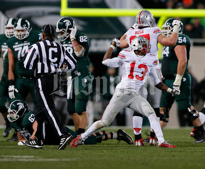 Ohio State Buckeyes cornerback Eli Apple (13) celebrates a fourth down stop during the third quarter of the NCAA football game against the Michigan State Spartans at Spartan Stadium in East Lansing, Michigan on Nov. 8, 2014. (Adam Cairns / The Columbus Dispatch)