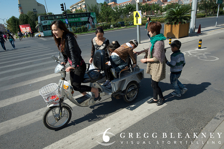 A family out for a Sunday pedal on a hybrid E-Bike along one of Beijing's many dedicated bicycle commuter lanes.