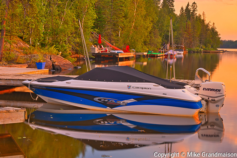Boat and docks at Star Lake at sunrise. Cottage Country Living.<br />