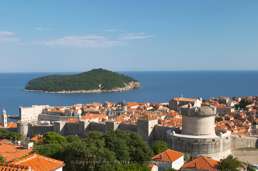 View from above of the old town with city walls and fort brick coloured rooftops roof tops, detail of wall an fortification tower with Lokrum island in the background, Minceta Tower Dubrovnik, old city. Dalmatian Coast, Croatia, Europe.