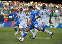El Salvador's Arturo Alvarez shoots and scores in front of Cuba's Hanier Dranguet (2) and Carlos Domingo Francisco (2).  El Salvador defeated Cuba 6-1 at the 2011 CONCACAF Gold Cup at Soldier Field in Chicago, IL on June 12, 2011.