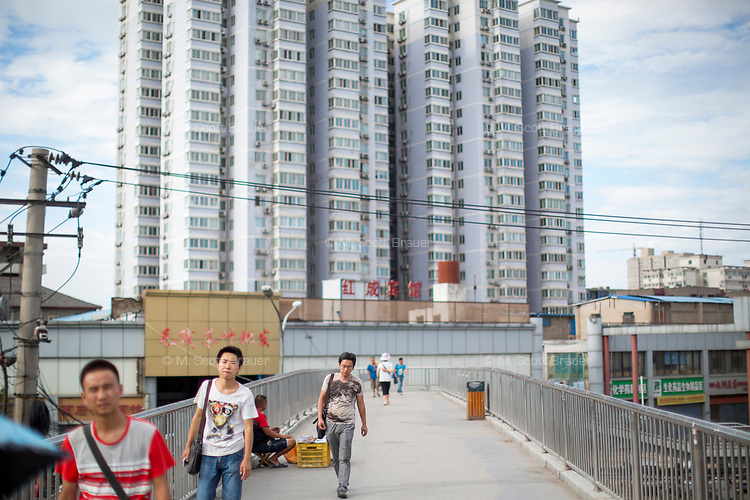 People walk on a pedestrian overpass under a tall apartment building in Xian, Shaanxi, China.