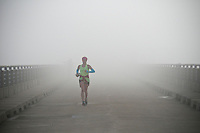 Jogger crossed Hoover Dam in an early morning fog.