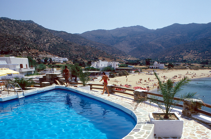 Hotel private pool in foreground and public beach in background on the island of Ios, Greece.
