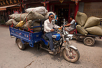 Daytime landscape view of a man driving a motorized tricycle on a road near the Chinese Herbal Medicinal Market in Bozhou in Qiáochéng Qū in Anhui Province.  © LAN