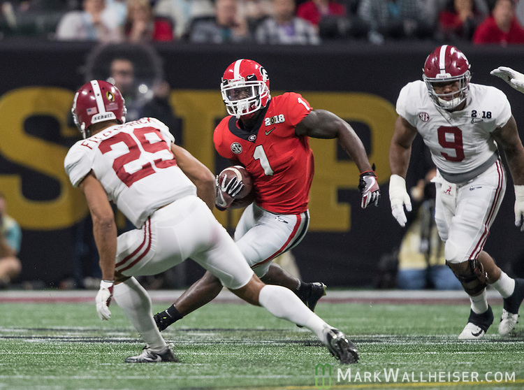 Georgia Bulldogs running back Sony Michel (1) makes a cut against Alabama Crimson Tide defensive back Minkah Fitzpatrick (29) as Alabama Crimson Tide defensive lineman Da'Shawn Hand (9) pursues in the first quarter of the NCAA College Football Playoff National Championship at Mercedes-Benz Stadium on January 8, 2018 in Atlanta. Photo by Mark Wallheiser/UPI