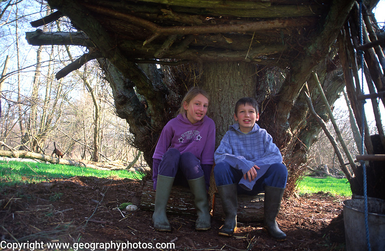 A082R5 Children playing at making den in woods