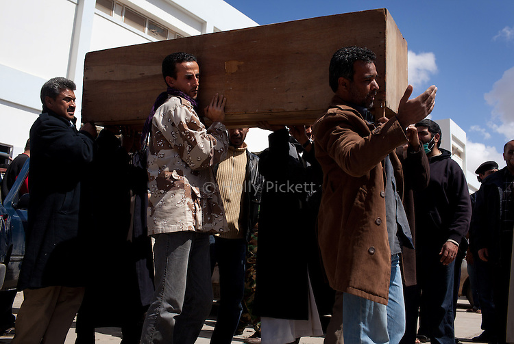 Men carry a coffin out of the hospital morgue in Benghazi, Libya, March 20, 2011. Family members prepared those killed during fighting between opposition rebels and loyalist forces of Col. Muammar Qaddafi for burial. The main hospital in Benghazi reported around 50 dead fighters and civilians the previous day and at least 35 on Sunday.