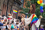 © Joel Goodman - 07973 332324 . 24 August 2013 . Manchester , UK . Giant Jesus with rainbow flag and balloons with gay Christians , shakes hands with the crowd . 2013 Gay Pride Parade through Manchester City Centre . This year's theme is 1980s . Photo credit : Joel Goodman