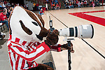Wisconsin Badgers mascot Bucky Badger plays with a photographer's camera during an NCAA volleyball match against the Michigan Wolverines at the Field House on October 30, 2010 in Madison, Wisconsin. Michigan won the match 3-1. (Photo by David Stluka)