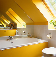 The size of this bright yellow bathroom built into the eaves of the house is visually enhanced by a mirrored wall beside the bath