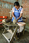 A master potter making red pottery in San Marcos Tlapazola  in her traditional satin dress and embroidered apron, typical to this town in the Central Valleys of Oaxaca, Mexico.  These traditional potters do not use a potter's wheel, but shape it all by hand.