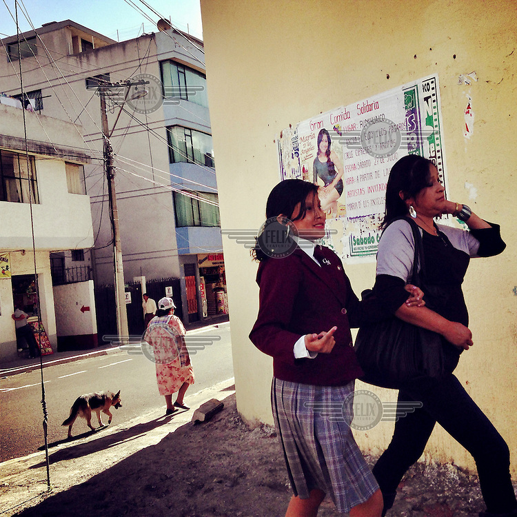 Two women walk together though Tumbaco.