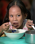 A girl enjoys a meal in the United Methodist Church in the Parola neighborhood of Tondo, a poor section of Maniila, Philippines. Nursing students from the Mary Johnston College of Nursing regularly visit the neighborhood to do health education and monitor the health of residents, at the same time running  a feeding program for neighborhood children.<br /> <br /> The nursing school is supported by United Methodist Women.