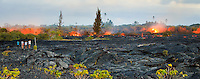 Spectators watch molten lava from Kilauea volcano flow over older land and foliage on the Big Island.
