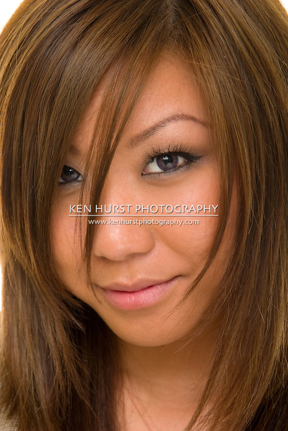 Extreme closeup of a beautiful young Asian brunette woman looking directly into camera.  Shallow depth-of-field with eye and lips in sharp focus.
