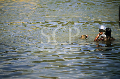 Bacaja village, Brazil. Xicrin woman washing an aluminium pot in river with a pet pig. Xicrin Indian tribe, Amazon.