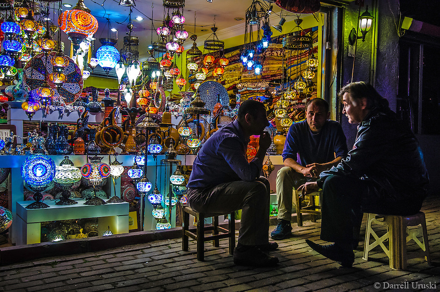 Fine Art Photograph. The colourful Mosaic lamps in Istanbul, Turkey. <br /> The warm low key lighting that is cast from the store lamps onto the faces of these local merchants while sitting on their stools sets the mood of this scene. <br /> Talking, watching, listening, thinking, each person is involved in the conversation in a different way.<br /> This print captures the heart and soul of a typical night in Istanbul, Turkey.