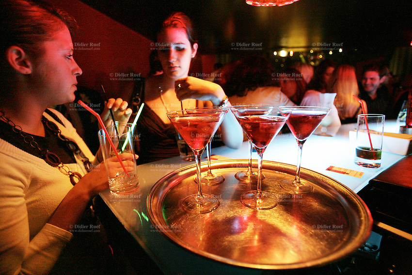 Switzerland. Canton Vaud. Lausanne. Red club. Exclusive and VIP party for the lauch of Xellent Vodka, the first and only Swiss Vodka. Two young girls have a drink at the bar . A tray with glasses full of cranberry juice mixed with vodka. Night life. © 2006 Didier Ruef