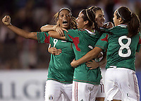 Maribel Dominguez of Mexico (L) and teammates celebrate during the semifinal match of CONCACAF Women's World Cup Qualifying tournament held at Estadio Quintana Roo in Cancun, Mexico. Mexico 2, USA 1.