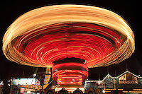 AUGUSTA, NJ - AUGUST 13: The colorfully illuminated Mini Wave Swinger spins against the night sky during the New Jersey State Fair on August 13, 2010 at the Sussex County Fairgrounds, Augusta, New Jersey