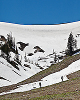 Hikers climbing the snow covered Fox Creek Pass in Death Cayon at the end of June.  Death Canyon is located in Grand Teton National Park, Wyoming.