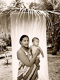 INDONESIA, Mentawai Islands, Kandui Resort,  portrait of young Indonesian woman holding her son (B&W)