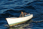 Old man motoring along in small fishing boat.