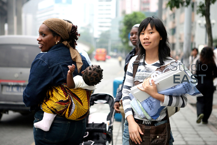 A Chinese woman reacts while an African woman carries her baby on her back, in Guangzhou, China, on March 15, 2007. Chinese goods flow to Africa, but men flow the other way: thousands of Africans are now settling in China. China's Southern metropolis Guangzhou has the country's largest African population, now exceeding 7,000. Photo by Patrick Wack/Pictobank