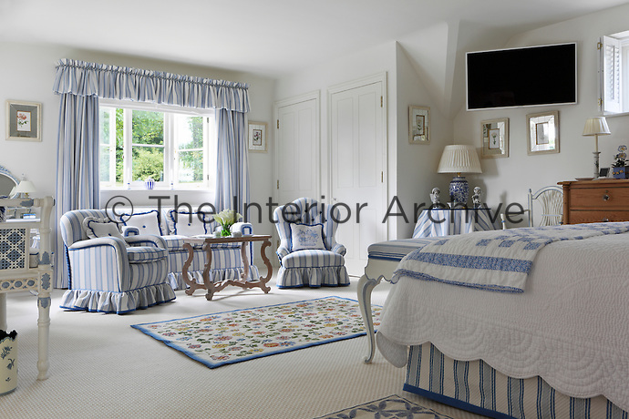 A blue and white guest bedroom with striped soft furnishings and a sofa and armchairs to make it comfortable for visitors