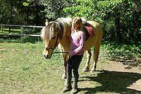 Mädchen beim Reitunterricht auf Ponyhof, Mädchen führt Reitpony an der Trense, Reiten, Reiterhof, Gestüt