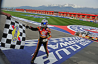 Feb 21, 2009; Fontana, CA, USA; NASCAR Camping World Truck Series driver Kyle Busch receives the checkered flag from an official after winning the San Bernardino County 200 at Auto Club Speedway. Mandatory Credit: Mark J. Rebilas-