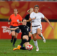 USWNT midfielder (11) Carli Lloyd is tackled by  New Zealand captain (8) Hayley Moorwood while playing at Wulihe Stadium. The USWNT defeated New Zealand, 4-0, during the 2008 Beijing Olympics in Shenyang, China.  With the win, the USWNT won group G and advanced to the semifinals.