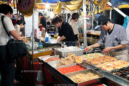 "July 8, 2014, Tokyo, Japan - A visitor enjoys eating at the ""Iriya Asagao-ichi Market Festival"" on July 8, 2014. The market festival was the most famous for asagao plants (morning glories) in Edo period, and has been held on July 6, 7, and 8 at the Temple of Iriya Kishimojin in Tokyo every year since late Edo period. The flower was introduced into Japan 1200 year ago from China for medical uses. (Photo by Rodrigo Reyes Marin/AFLO)"