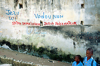 "Haiti. Province of Ouest. Port-Au-Prince. Slum of Campêche. Highly densely populated. Two brothers dressed with their blue blue uniforms on the way to school. The writing on the wall says: "" The devil destroys, Jesus Christ repairs"" and ""Jesus Christ yes, Voodoo cult no !"".  © 2003 Didier Ruef"