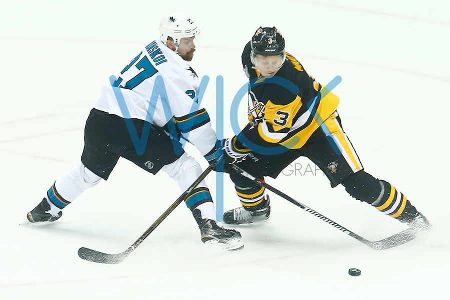 Olli Maatta #3 of the Pittsburgh Penguins and Joonas Donskoi #27 of the San Jose Sharks reach for the loose puck in the second period during game one of the Stanley Cup Final at Consol Energy Center in Pittsburgh, Pennslyvania on May 30, 2016. (Photo by Jared Wickerham / DKPS)