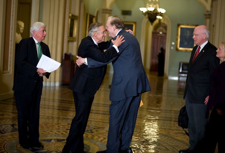 Senate Majority Leader Harry Reid, D-Nev., left, hugs Sen. John Rockefeller, D-W.V., after the Senate voted to begin debate on health care legislation as Sen. Chris Dodd, D-Conn., left, Sen. Patrick Leahy, D-Vt., and his wife Marcelle, look on, Nov. 21, 2009.