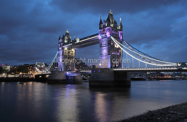 Tower Bridge at night, built 1886-94, seen from the South bank opposite the Tower of London on the river Thames, linking the boroughs of Southwark and Tower Hamlets, London, England. The bridge is both suspension bridge and bascule bridge, with the lower section rising using hydraulic motors to allow for the passing of boats. It is 244m long with 2 65m towers built on piers in the river. Picture by Manuel Cohen