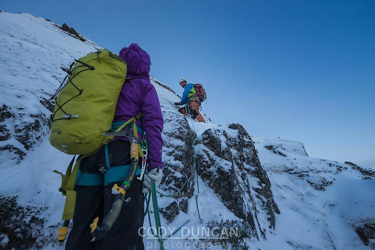 Climbing team ascending steep snowy rockface, Vestvågøy, Lofoten Islands, Norway