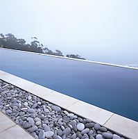 Long infinity pool positioned along the edge of a mountain with a misty sea view