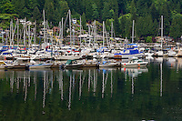 Yachts and pleasure craft reflected in the cove, with the background of houses overlooking Deep Cove, North Vancouver, British Columbia, Canada.
