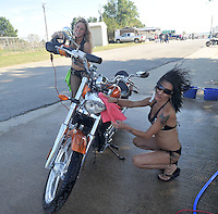 NWA Democrat-Gazette/MICHAEL WOODS • @NWAMICHAELW<br /> Michelle Stroud (from left) and Kim Whisler both from Kansas City, have some fun as they dry off a motorcycle Friday September 25, 2015 at the bikini bike wash at the Washington County Fairgrounds in Fayetteville. The bikini bike wash will be open at the Fairgrounds through out the bike rally.  The 16th annual Bikes, Blues and BBQ Motorcycle Rally runs through Saturday on Dickson Street, Baum Stadium and the Washington County Fairgrounds in Fayetteville and all day Saturday at Arvest Ballpark in Springdale.