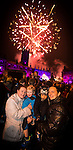© Joel Goodman - 07973 332324 . 17 November 2013 . Oldham , UK . L-R Mum Helen Schofield with son Oliver Hilton (two) and mum Kim Schofield (Helen's sister) with her son  Gelnroy Bailey (one) (all correct) . The crowds enjoy the fireworks . The Christmas lights are turned on in Oldham Town Centre . Photo credit : Joel Goodman