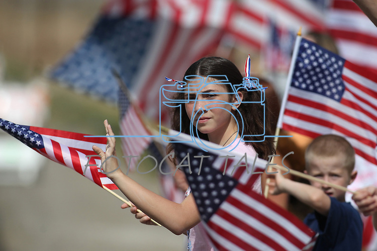 Sarah Gregory, 13, of Reno, was among an estimated 400 supporters who lined the streets outside a memorial service in Carson CIty, Nev., on Sunday, Sept. 11, 2011, honoring three Nevada National Guard members who were killed earlier this week by a gunman in an IHOP restaurant. (AP Photo/Cathleen Allison)