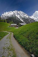 Mountain huts below snow capped mountain, Hahntennjoch pass Imst district, Tyrol, Tirol. Austria.